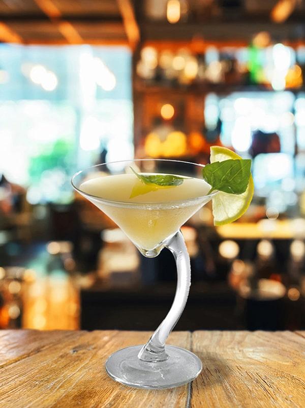 cocktail pomme maudite dans verre à pied avec menthe et citron