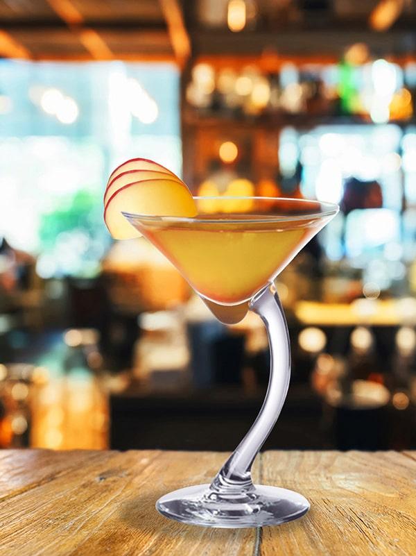 cocktail azuleja dans verre à pied avec décoration de quartiers de pommes