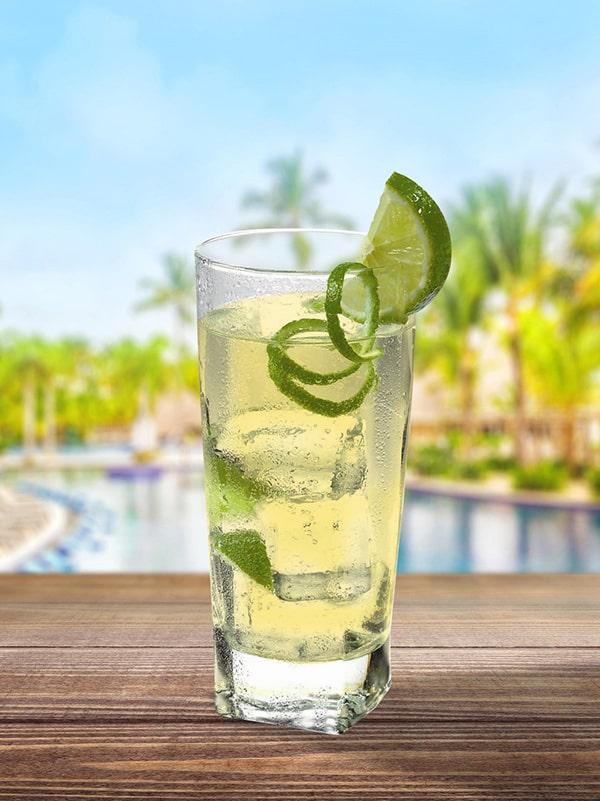 Cocktail Tequila Collins sur fond de piscine