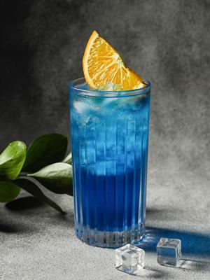 Cocktail Blue Lagoon dans un verre avec des glaçons, brochette de citron et zeste de citron