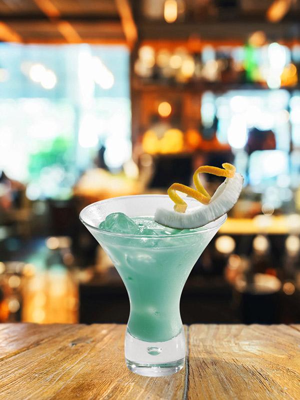 cocktail blue mountain dans un verre avec de la glace pilée, zeste de citron et morceau de noix de coco