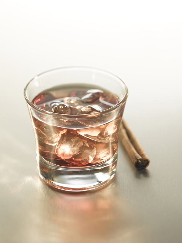 cocktail cinammon delice dans un verre avec des glaçons et un bâtonnet de cannelle