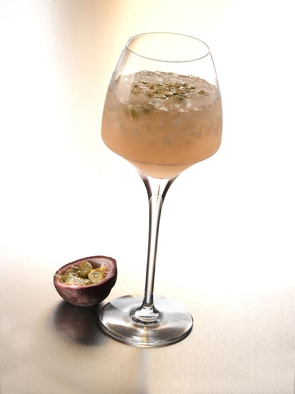 cocktail reve estival dans un verre à pied avec glace pilée et fruits de la passion