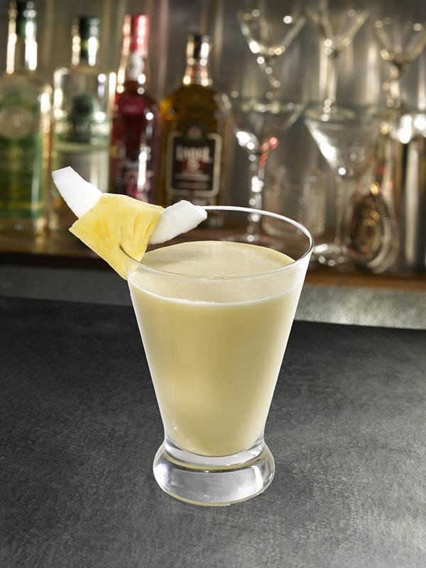 cocktail virgin colada dans un verre avec morceau d'ananas et noix de coco