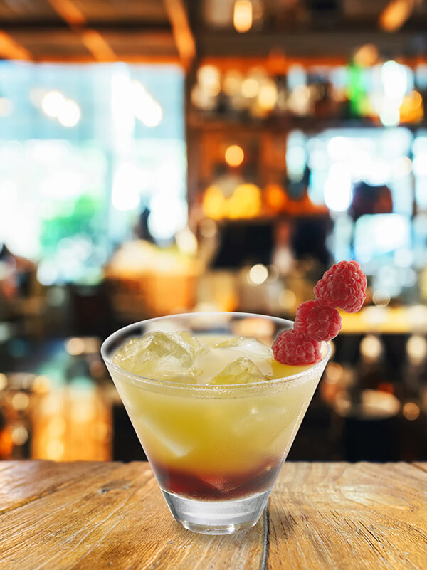 cocktail atlantis dans un verre avec de la glace pilée et une brochette de framboise