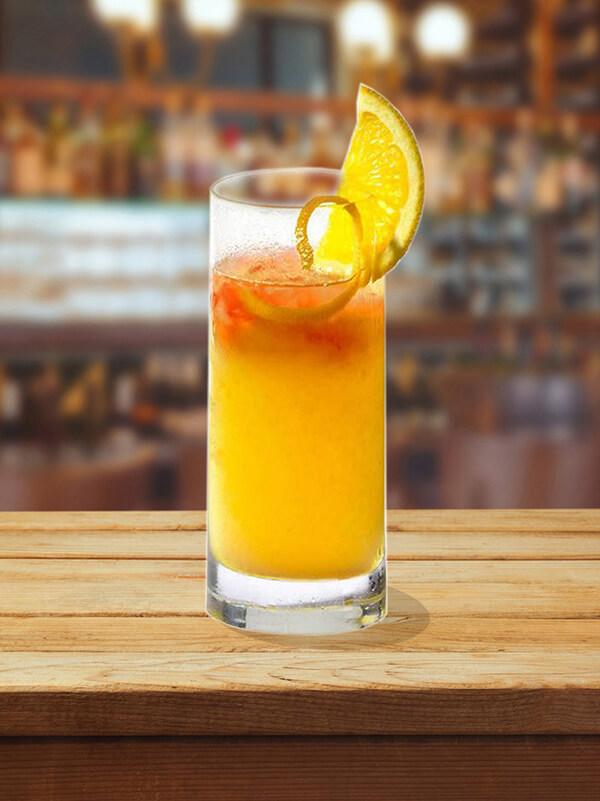 cocktail gk sunrise dans un verre avec de la glace pilée, tranche de citron vert et zeste de citron