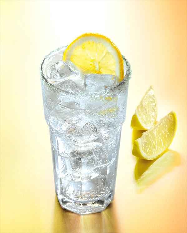 cocktail rhum tonic dans un verre avec de la glace pilée et des tranches de citron