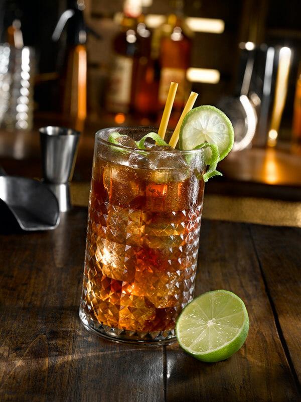 cocktail spiced cola dans un verre avec des glaçons et du citron vert