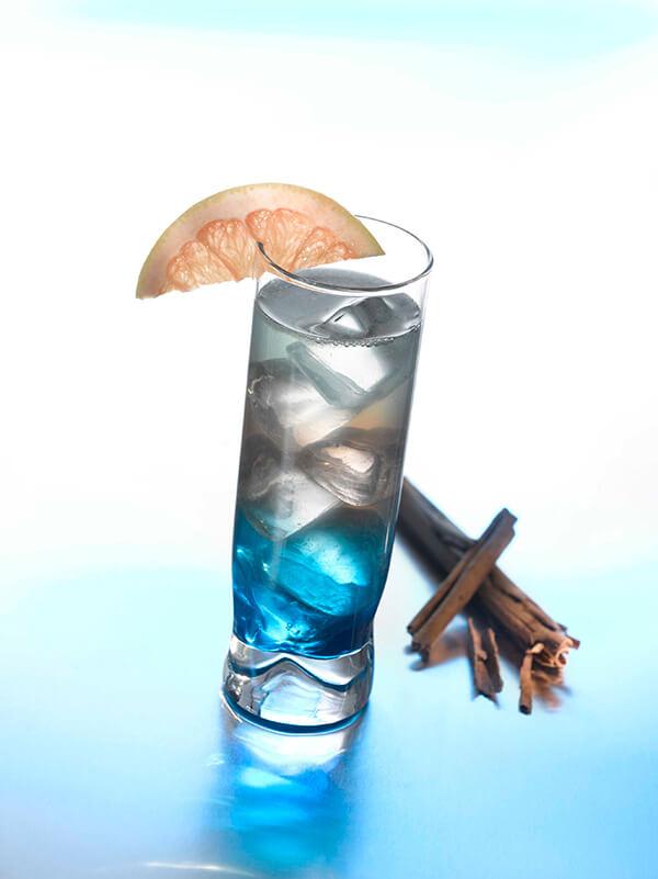 Cocktail le nuancier dans un verre avec des glaçons avec une branche de cannelle et une tranche de citron