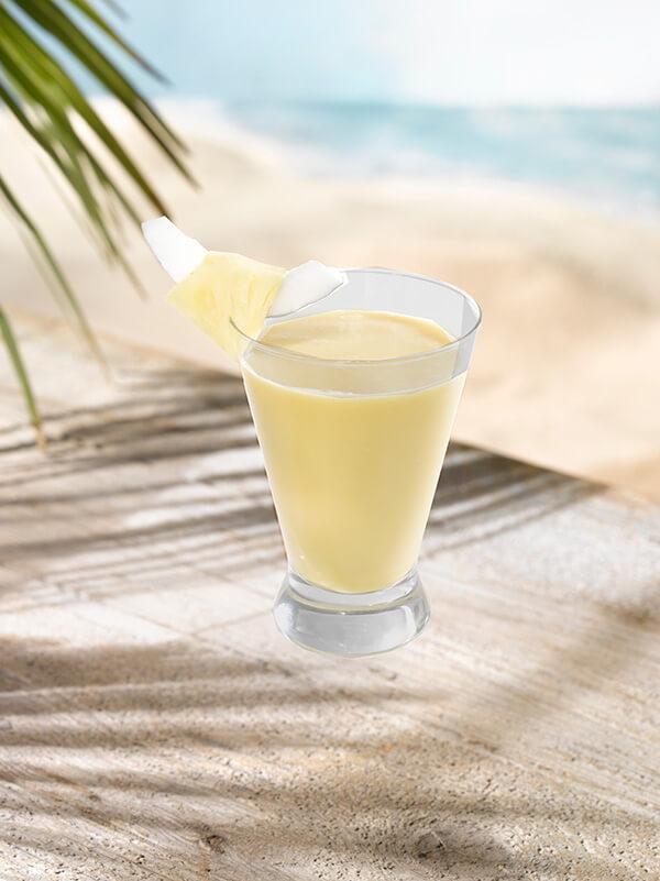 Cocktail spicy colada dans un verre avec morceau d'ananas et de noix de coco