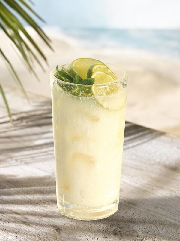 Cocktail mojito colada dans un verre avec glace pilée, menthe fraiche et tranches de citron vert