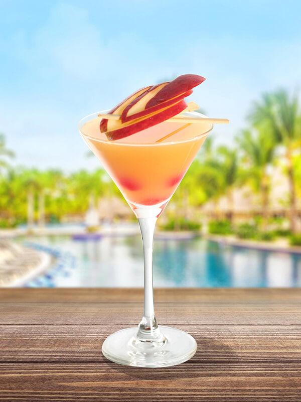 Cocktail ginger aphrodite dans un verre à pied avec morceau de pommes et de framboise