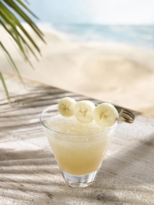 Cocktail caramel antillais avec de la glace pilée et une brochette de banane