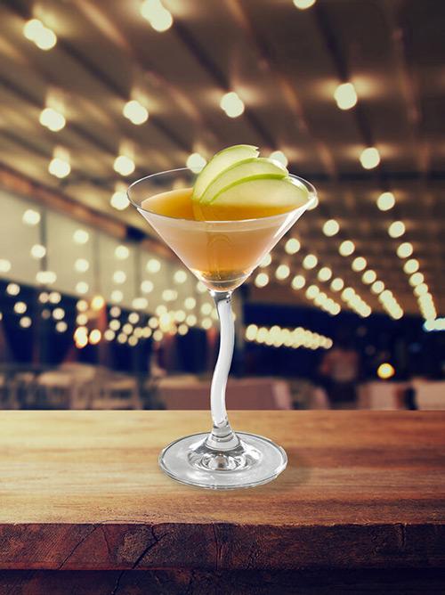 Cocktail delice dans un verre à pied avec tranches de pomme verte