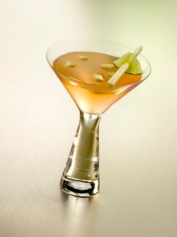 Cocktail so peachy dans un verre à pied avec du citron vert