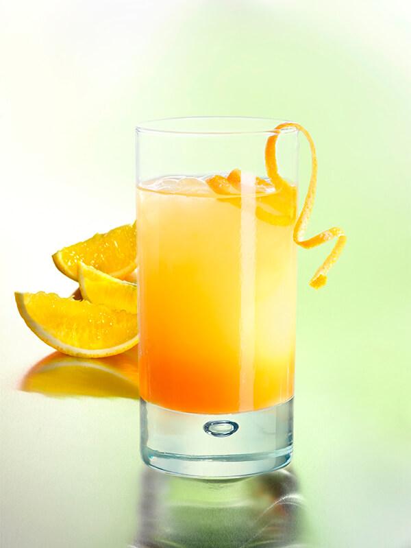 Cocktail orange blosson dans un verre avec des zeste et morceaux d'orange