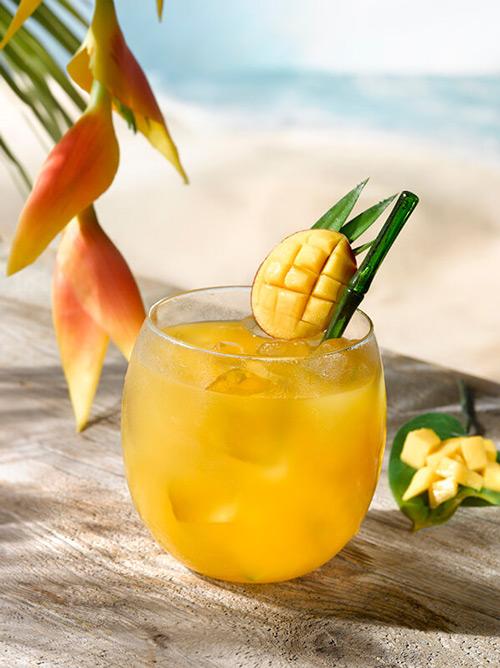 Cocktail batida de manga dans un verre rond avec glaçons et morceaux de fruits