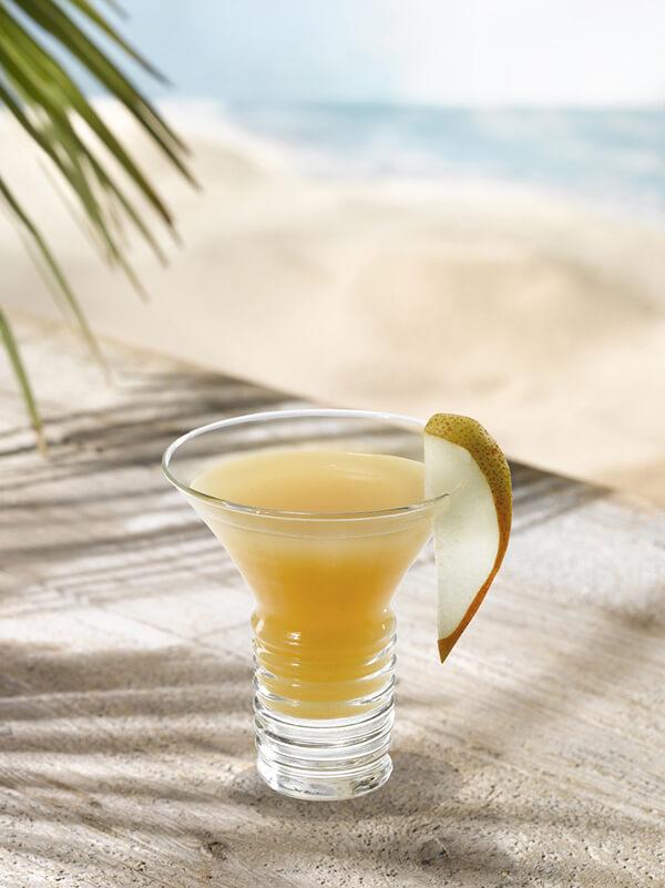 Cocktail karamello dans un verre à pied avec une tranche de poire