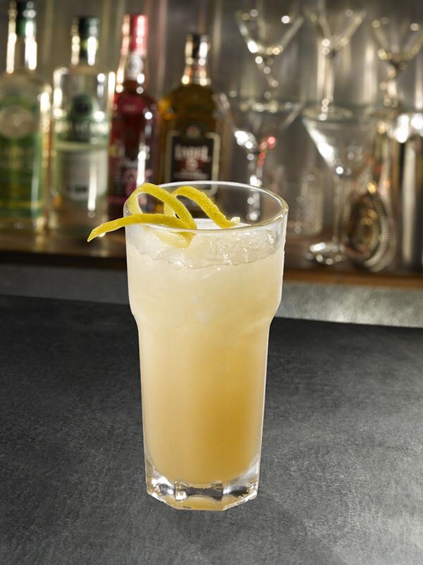 Cocktail el mundo dans un verre avec de la glace pilée et un zeste de citron