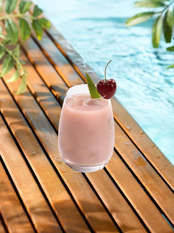 Cocktail smoothie pinky dans un verre avec glaçons et cerise entière