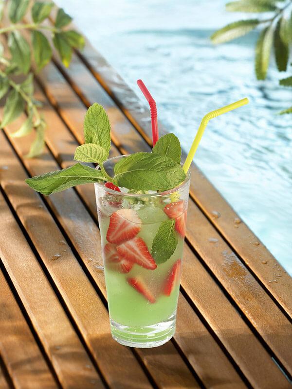cocktail fresh fruit dans un verre avec des glaçons, des morceaux de fraise et des feuilles de menthe