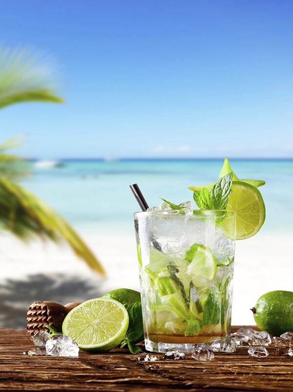 Cocktail virgin mojito dans un verre avec de la glace pilée, des feuilles de menthe, du citron vert. Sur un fond de plage tropicale ensoleillée