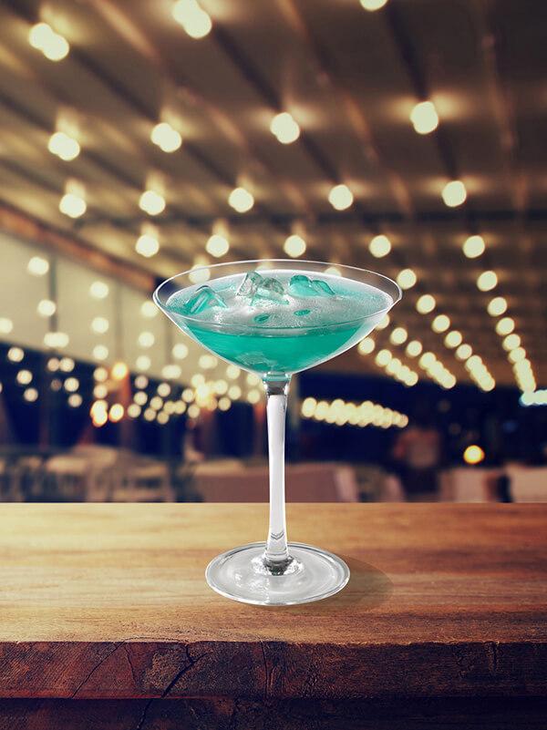 Cocktail blue up dans un verre à pied avec glace pilée