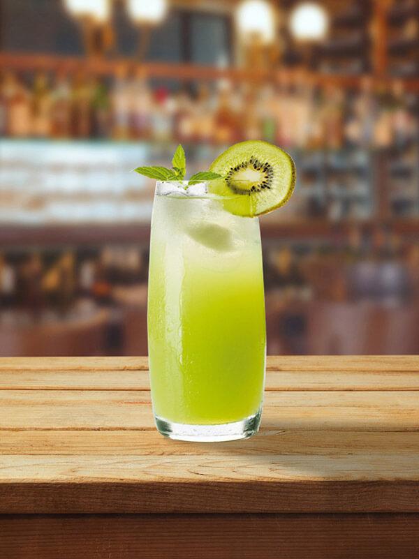 Cocktail aphrokiwi dans un verre avec des glaçons, une tranche de kiwi et une feuille de menthe