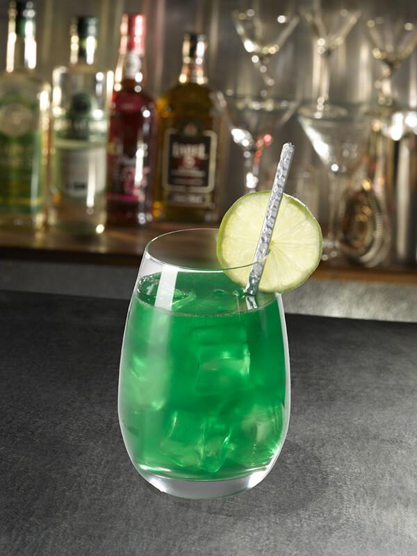 Cocktail blanc bec menthe dans un verre avec des glaçons, une paille et des tranches de citron vert