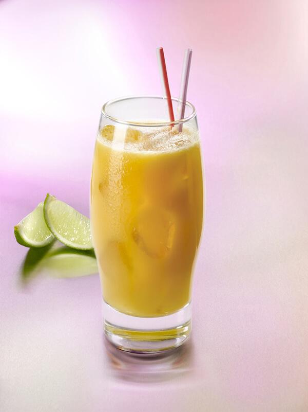 Cocktail fleur d'amour dans un verre avec des glaçons, deux pailles et du citron vert
