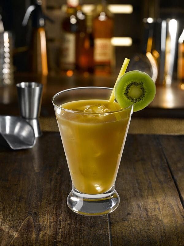 Cocktail fruits des iles dans un verre avec des glaçons, une paille et une tranche de kiwi
