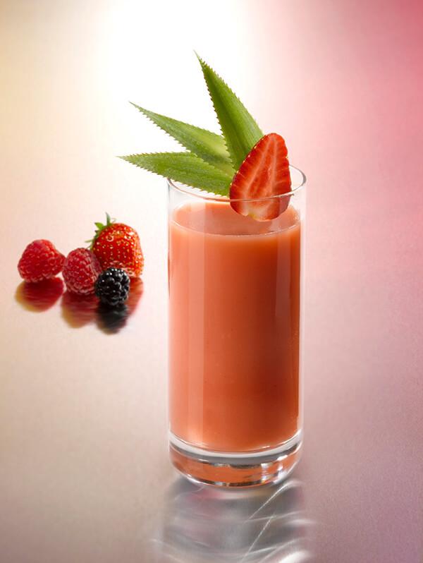 Cocktail redlight dans un verre avec une fraise, une mûre et deux framboises