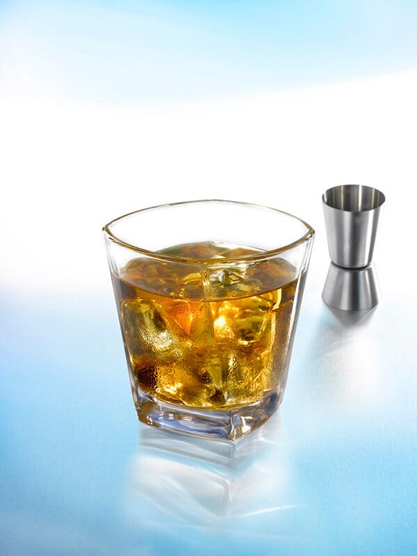 Cocktail godfather dans un verre à whisky avec des glaçons et un verre doseur