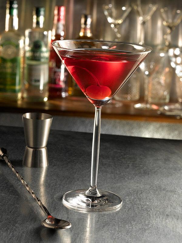Cocktail manhattan dans un verre à pied avec une cerise, verre doseur et cuillère