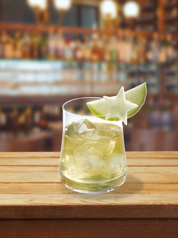 Cocktail apple tree dans un verre avec des glaçons, du citron vert et de la carambole