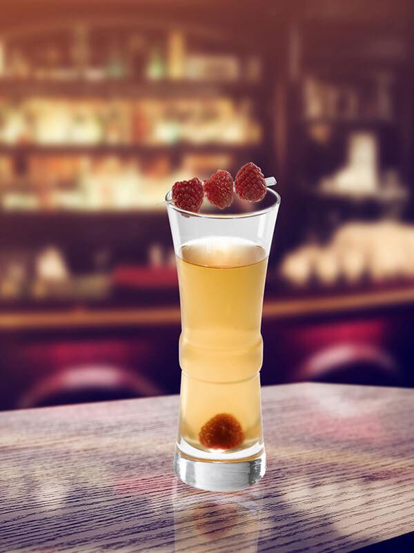 Cocktail edouard dans un verre avec une brochette de framboise et framboise entière
