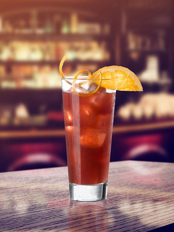 Cocktail red purple dans un verre avec des glaçons, zeste et morceaux de citron