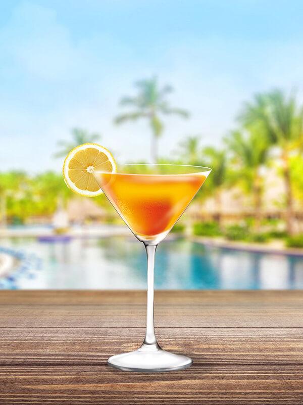 Cocktail ginger passion dans un verre à pied avec tranche de citron