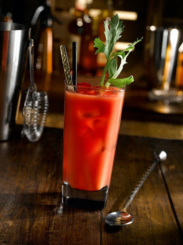 Cocktail bloody mary dans un verre avec paille, cuillère et branche de céleri