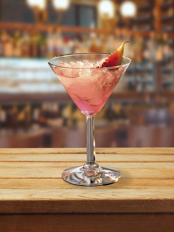 Cocktail fresh pink dans un verre à pied avec de la glace pilée et morceau de figue