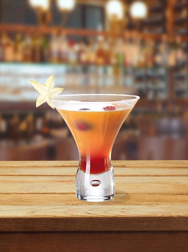 Cocktail sweet william dans un verre avec des framboises et de la carambole