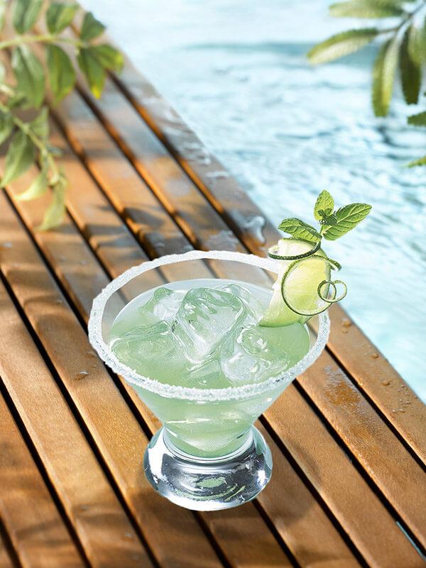 Cocktail blue moon dans un verre avec du sucre sur le bord, des glaçons, une tranche et un zeste de citron vert et une feuille de menthe