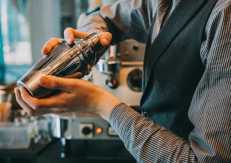 Barman professionnel utilise shaker avec ses deux mains