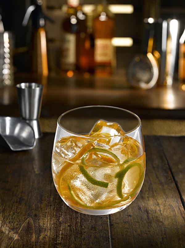 Cocktail 59 zest dans un verre avec glaçons et zestes de citron et citron vert