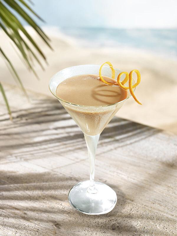 Cocktail alexan dillon dans un verre à pied avec zeste d'orange