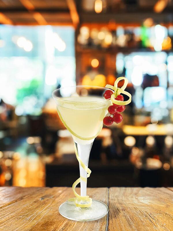 Cocktail amour dans un verre à pied avec des zestes de citron et une grappe de groseille