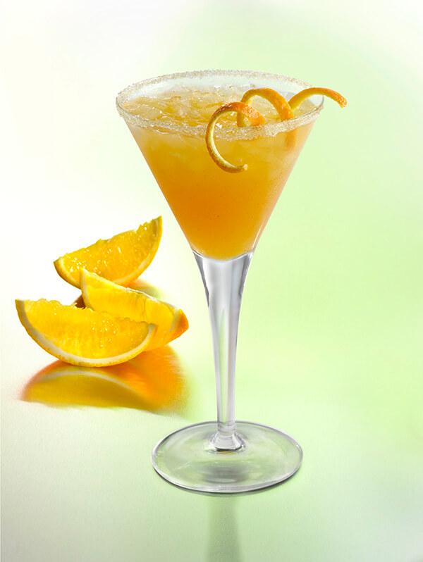 Cocktail barba rosa dans un verre à pied avec de la glace pilée, zeste d'orange et des quarts d'orange