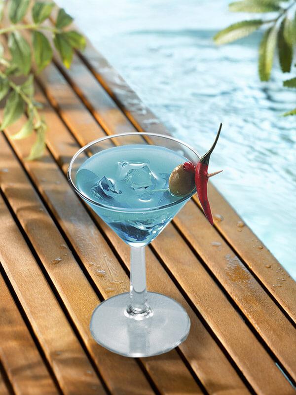 Cocktail blue apple dans un verre à pied avec des glaçons, olive, poivron et piment