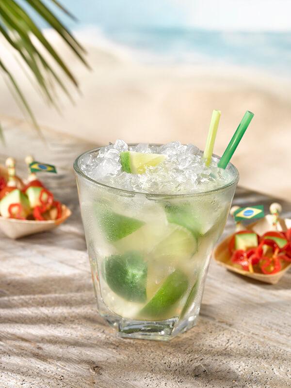 Cocktail caipirinha dans un verre avec glace pilée, quarts de citron vert et deux pailles