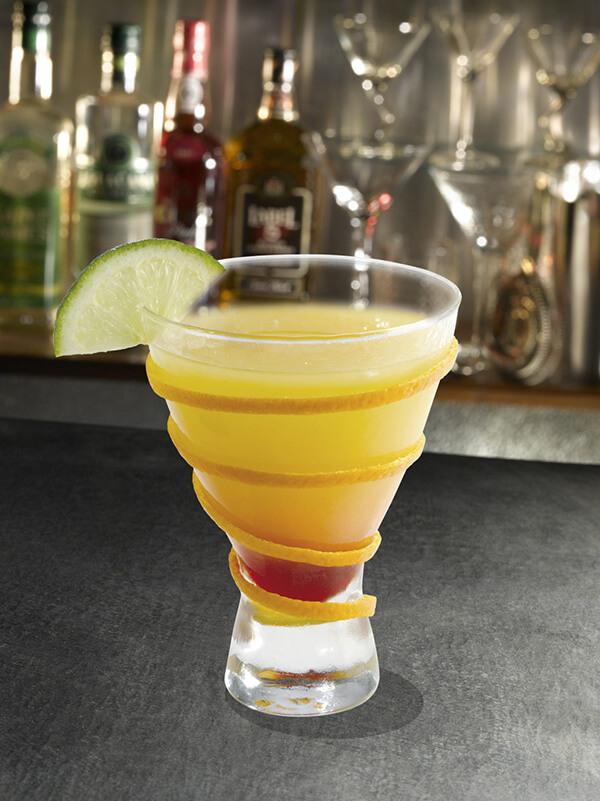 Cocktail cendrillon dans un verre à pied avec des zestes de citron et une tranche de citron vert